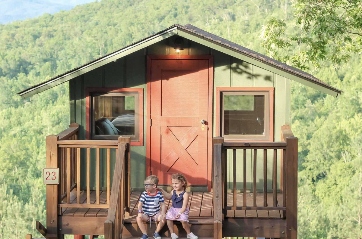 Two children sitting in front of a treetop cabin
