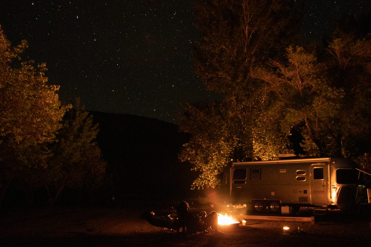 While RVing, two people sit and stare at the stars in front of their Airstream trailer at Capitol Reef National Park in Utah.