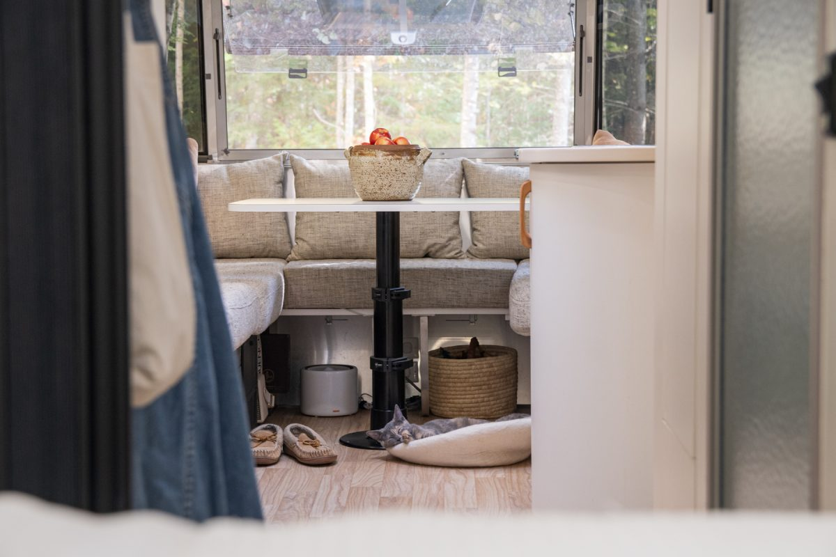 A cat sleeps on a bed on the floor of an RV trailer. On top of the dinette above the cat there is a bowl full of apples.