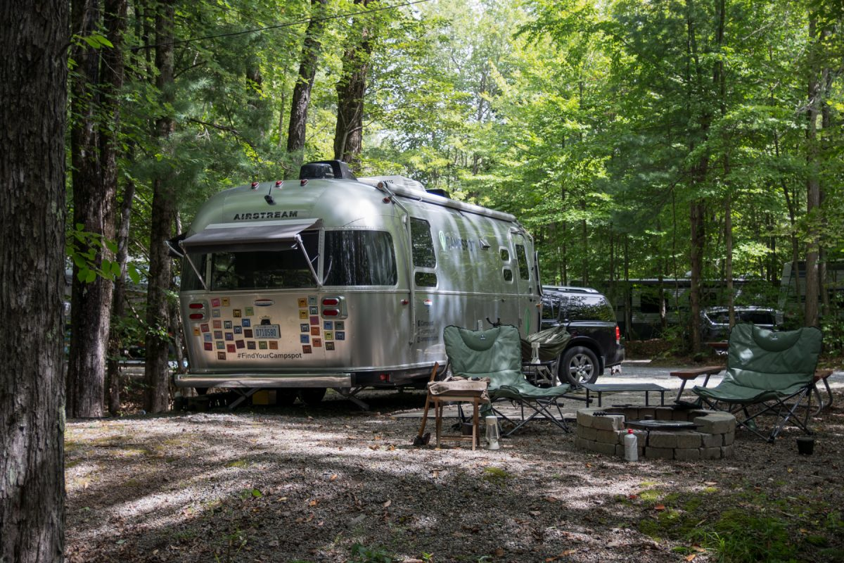 An Airstream trailer with a bunch of bumper stickers sits in a wooded area with two camper chairs in front of it.