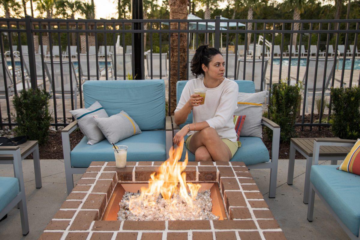 Campspot Ambassador, Kendra lounging outside by a fire at Carolina Pines.