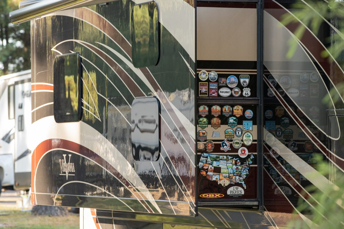 A collection of National Parks stickers are gathered on a slide-out of an RV trailer.