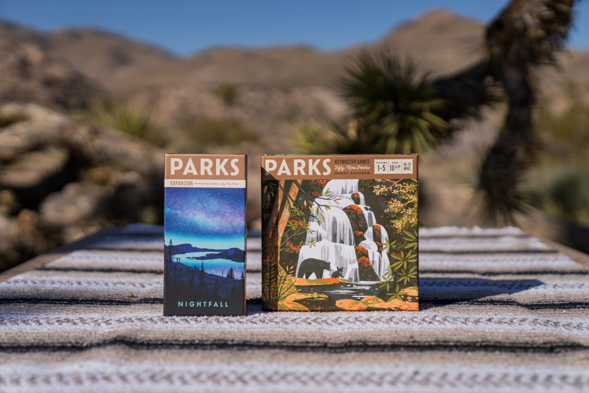 The PARKS board game and its Nightfall Expansion pack sit on top of a picnic table at Joshua Tree National Park in California.