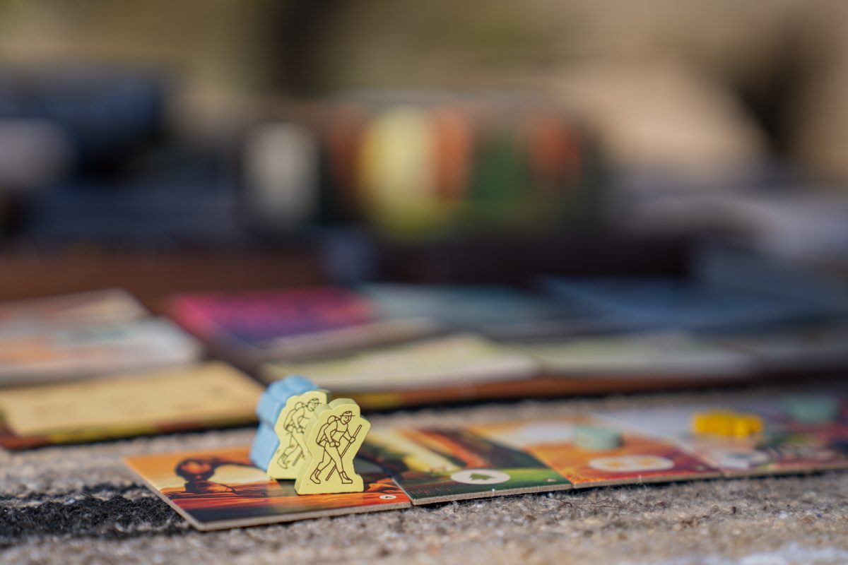 Two game pieces representing hikers sit on top of the trailhead card of the PARKS board game created by Keymaster Parks and the Fifty-Nine Parks Print Series in celebration of National Parks.