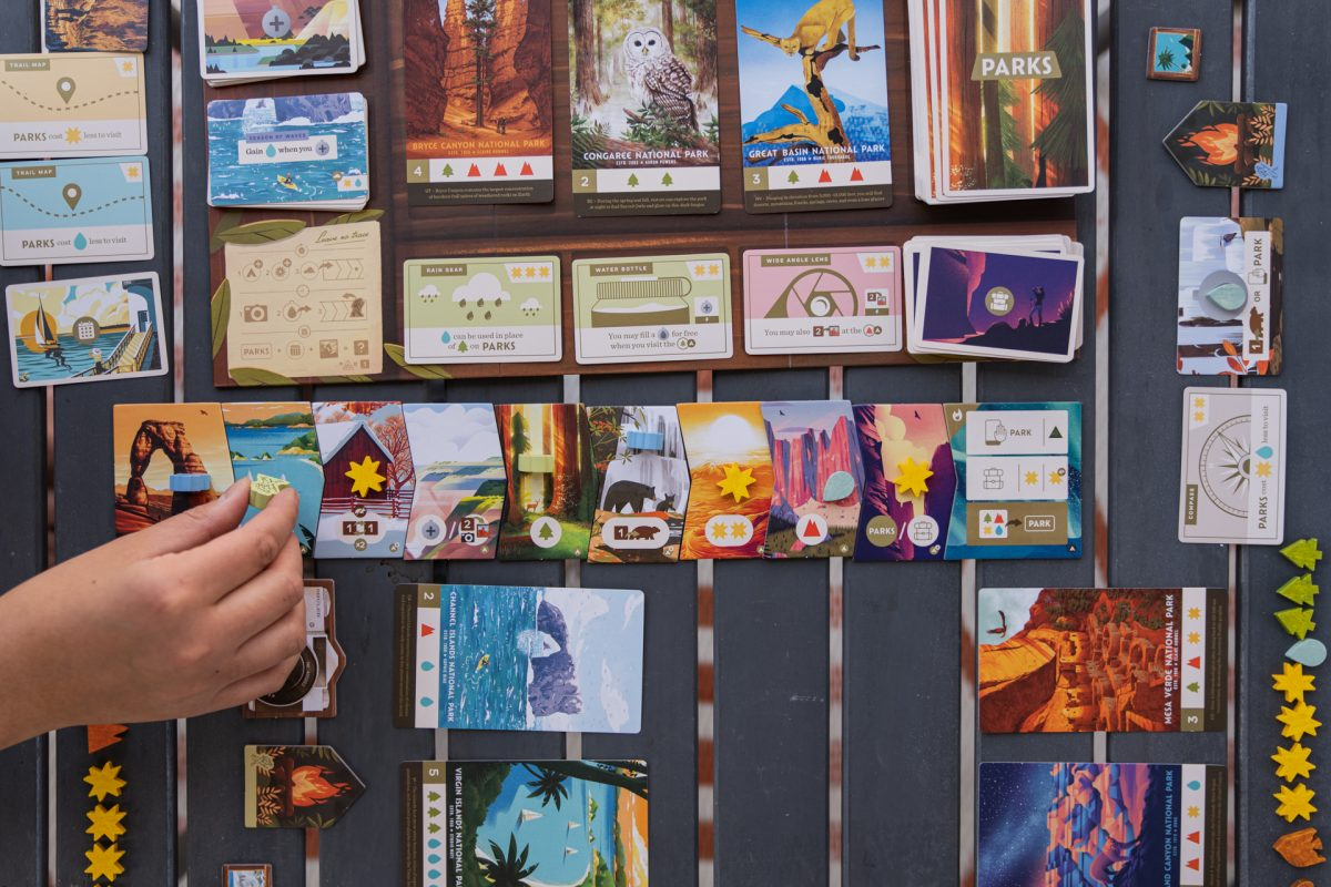A person's hand moves their hiker while playing the PARKS board game that Keymaster Games and the Fifty-Nine Parks Print Series made together in celebration of National Parks.