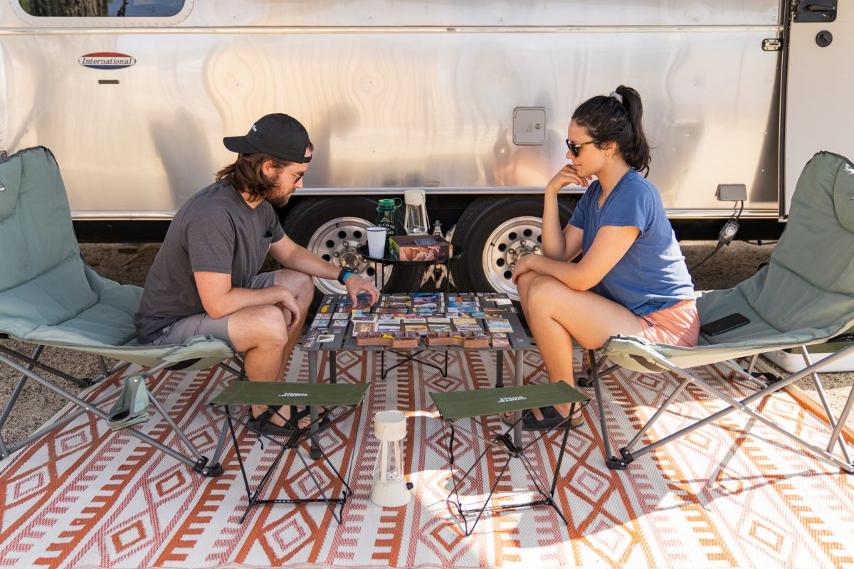 A couple sit outside in front of their Airstream trailer playing a board game.