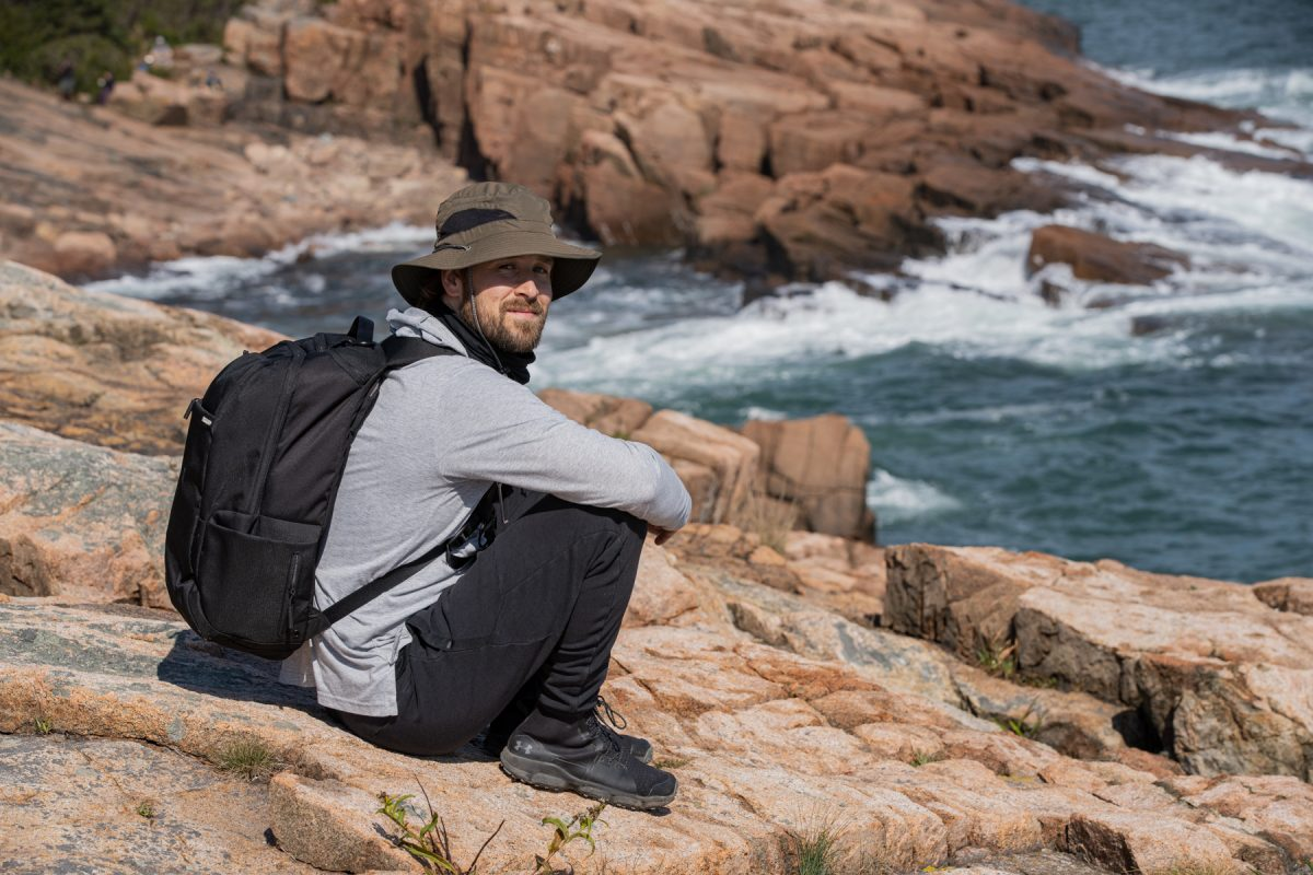 A man sits along the jagged rocks at Acadia National Park in Maine.
