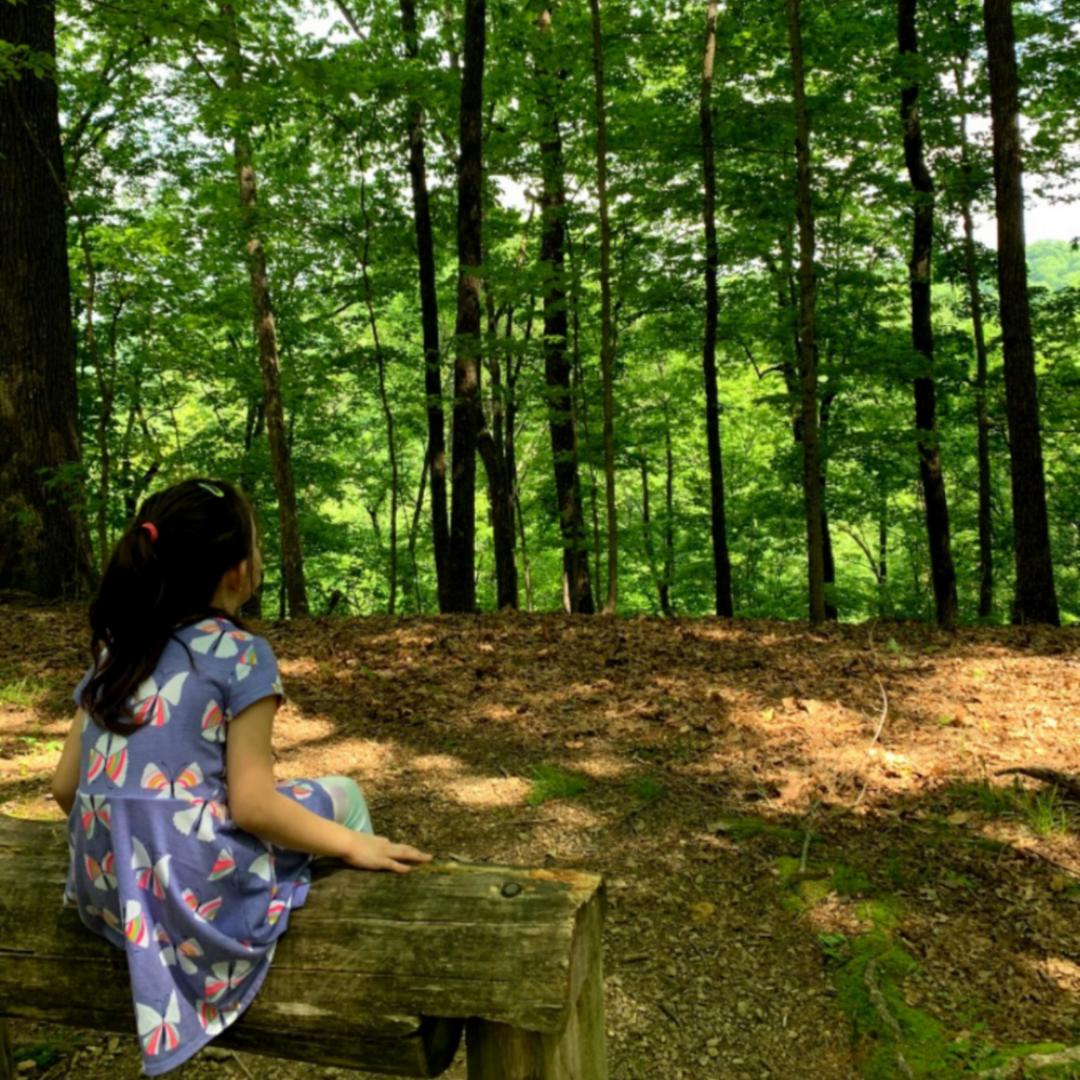 Girl sitting on bench enjoying the woods.