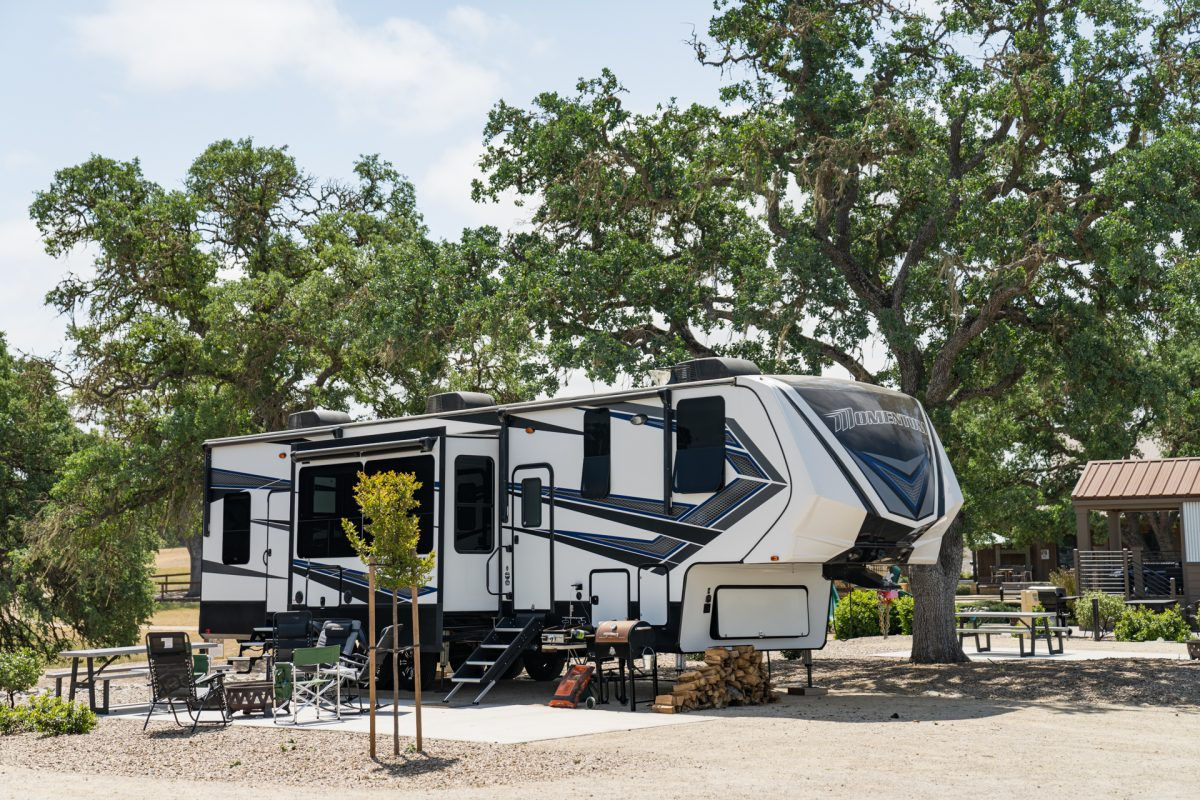 A fifth-wheel trailer sits underneath old oak trees at the Cava Robles RV Resort in Paso Robles, California.