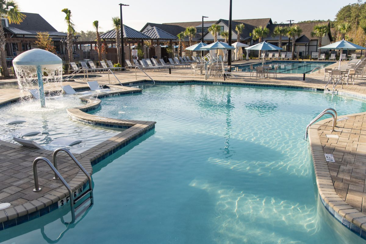 Pool area with palm trees and club house in the background at Carolina Pines RV Resort