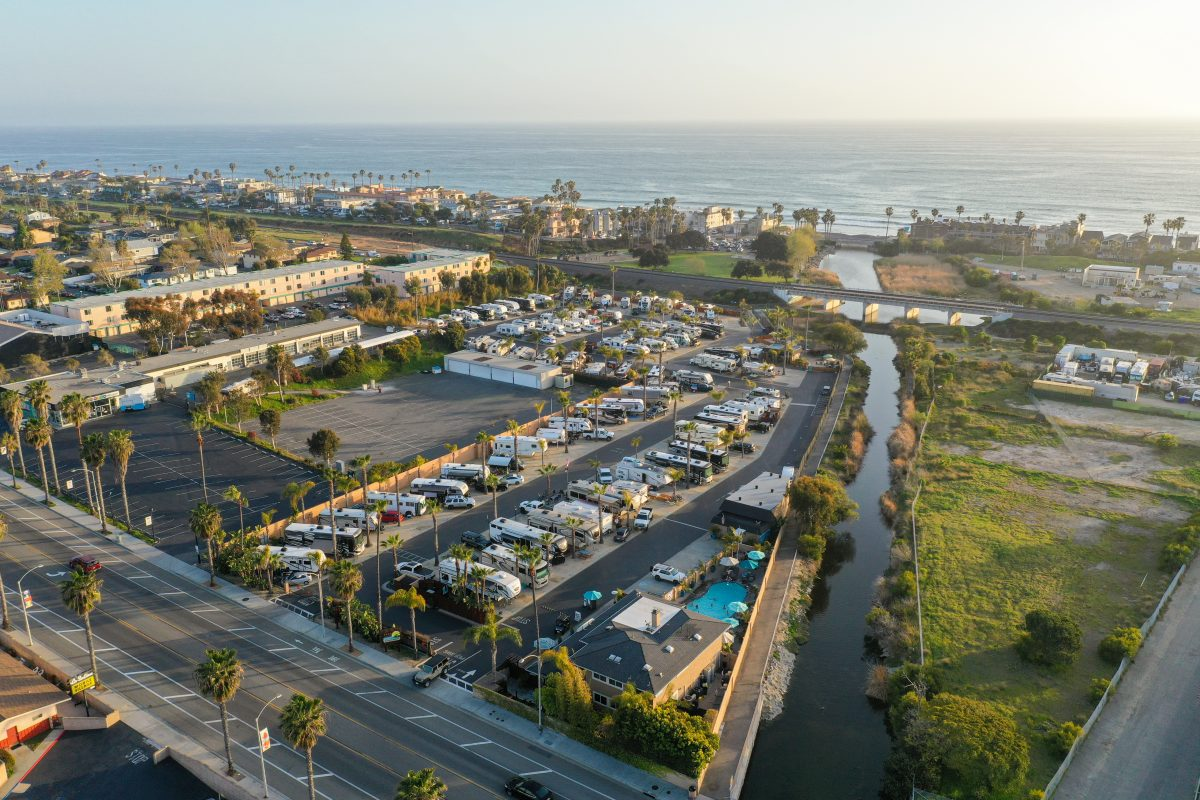 Ariel photo of paradise by the sea RV resort with RVs and the ocean in the background.