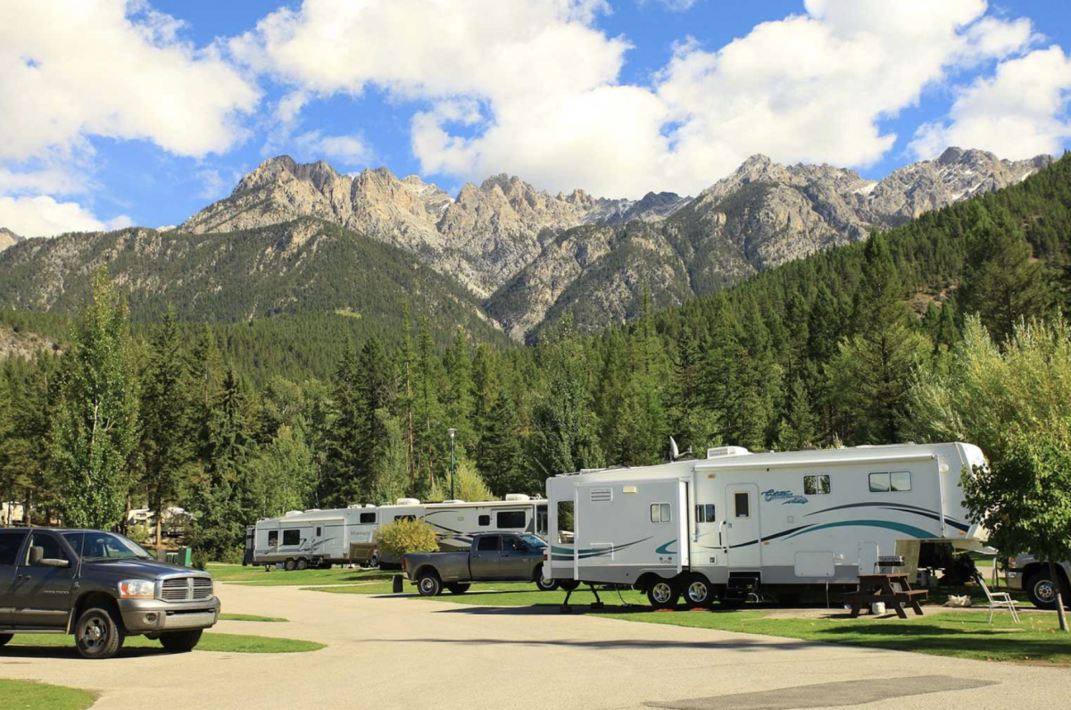 RV parked in front of mountain at campground.