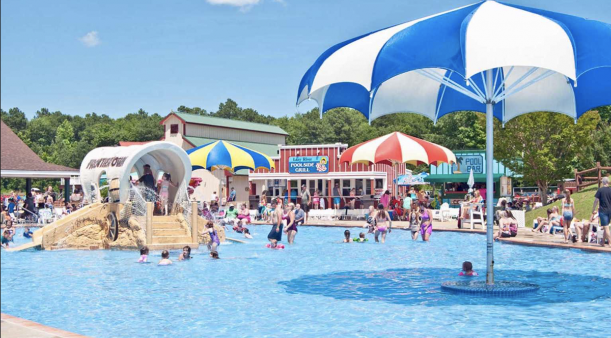 Pool area at Frontier Town RV Resort with giant umbrellas and kids playing in the pool.