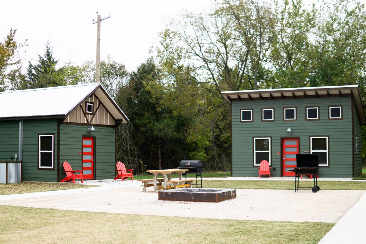Luxury green cabins with red doors and a fire pit at Hidden Grove RV Resort in Texas.