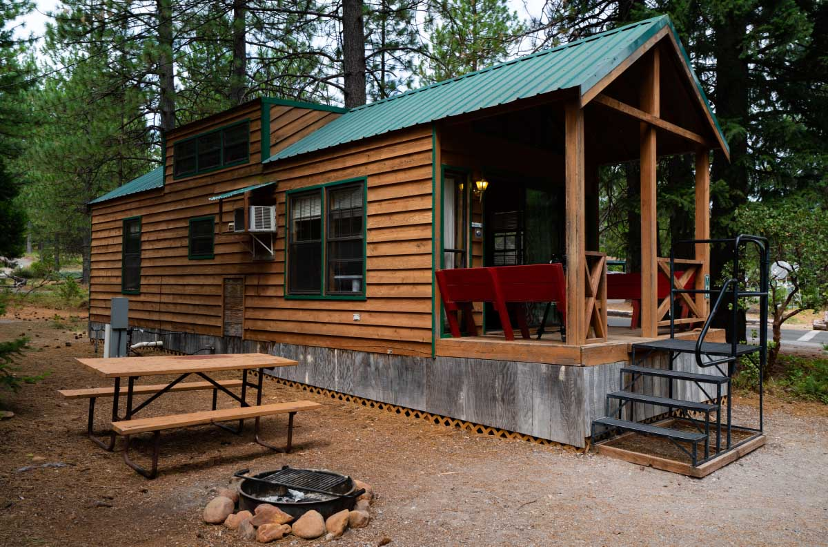 Cabin in the woods with picnic table and fire place at Lake Siskiyou Camp Resort.