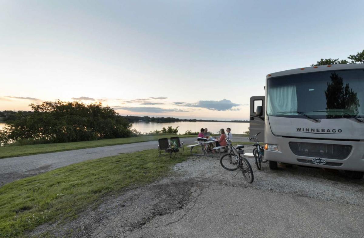 Winnebago parked next to lake at Lake Shawnee Campground.