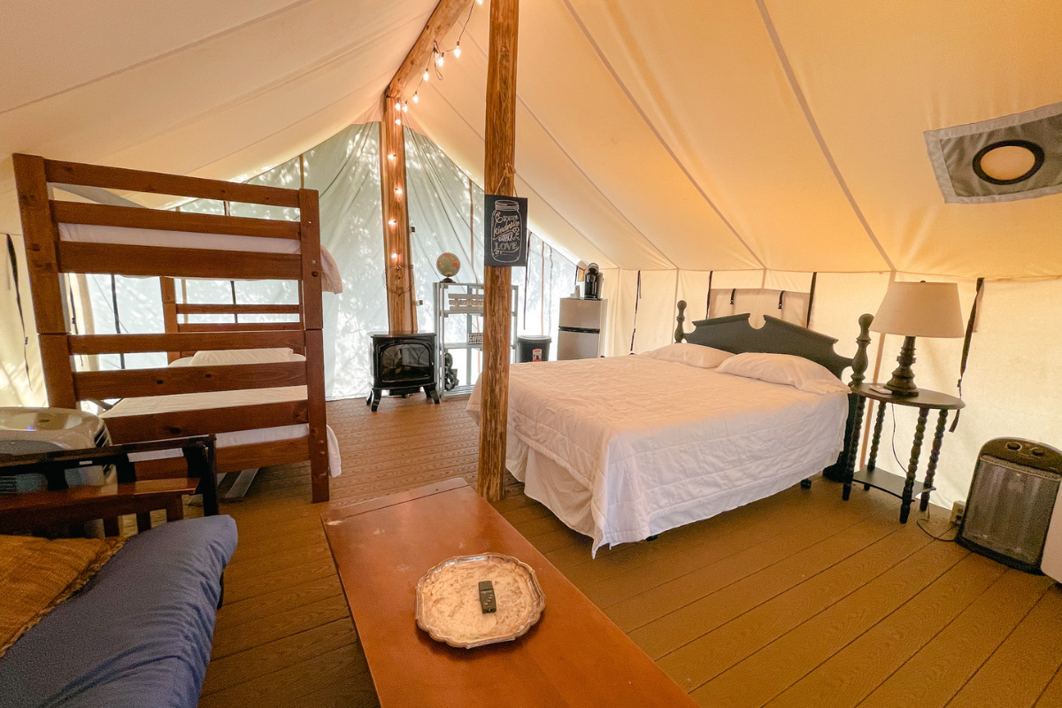 Inside of a glamping tent with a queen bed and bunk beds