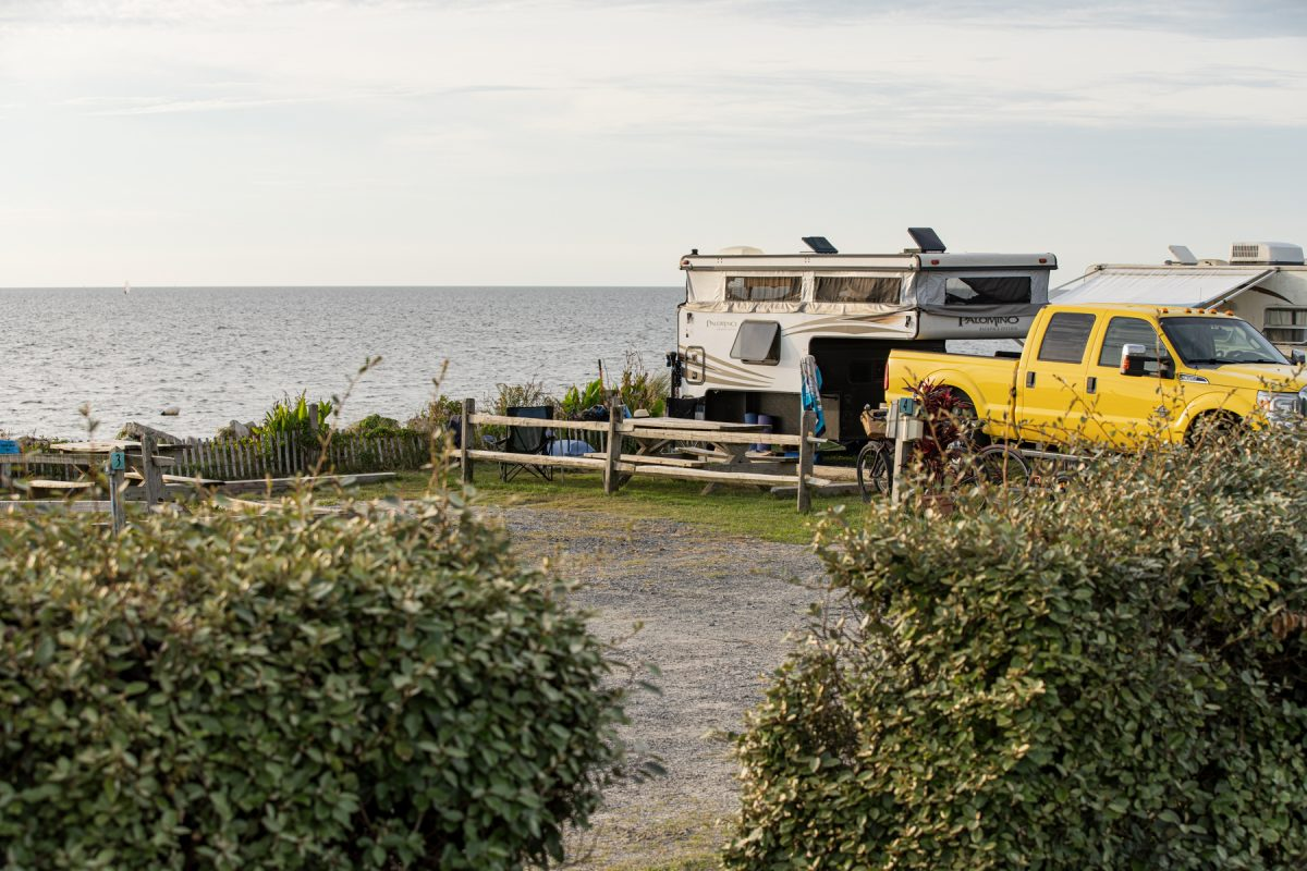 A pop up camper sits at a campsite along the water at Rodanthe Watersports and Campground in Rodanthe, NC.