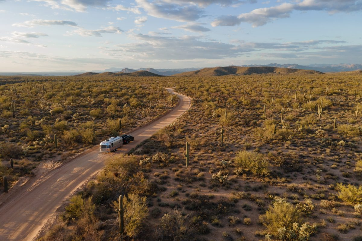 An SUV pulling an Airstream trailer goes through a forest of saguaro cacti in Arizona.