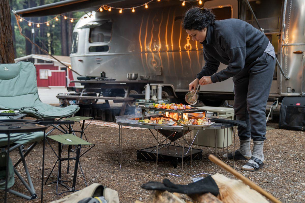 A camper prepares screwers on a Snow Peak campfire.