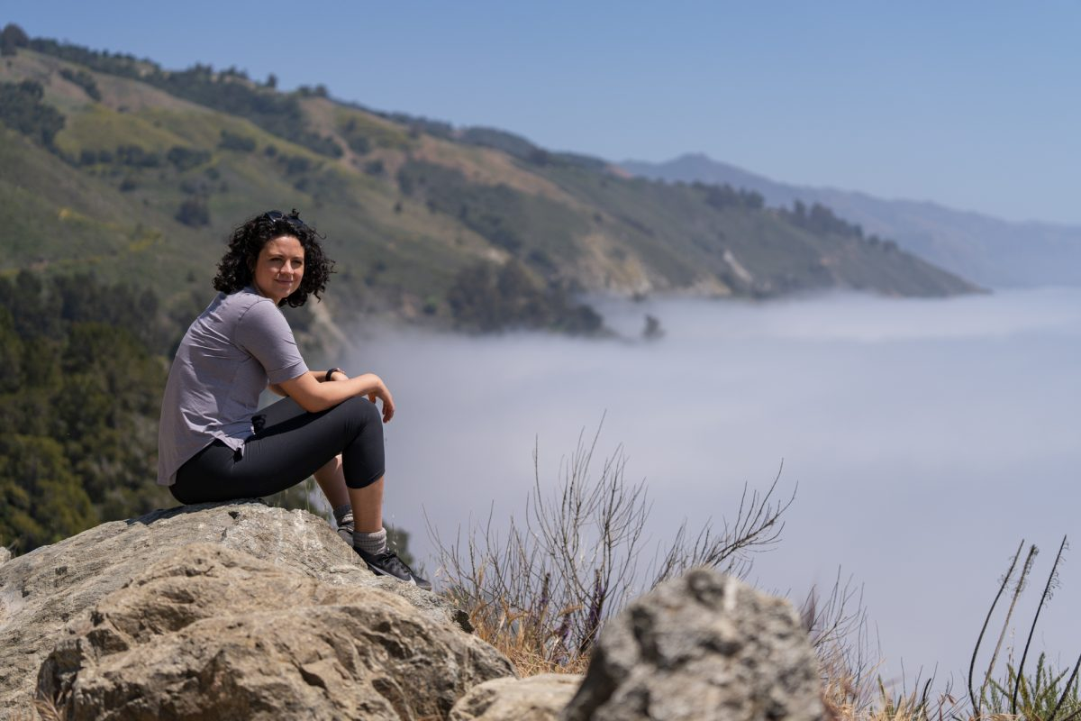 A woman looks out to the cloud covered ocean in Big Sur, CA.