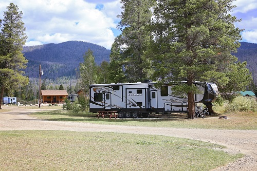 RV parked at Winding River Resort with mountains in the background.