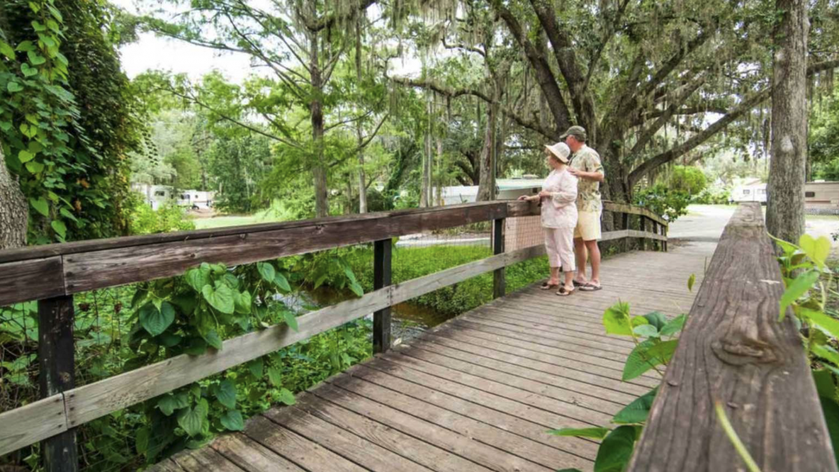 A couple walks on the boardwalk at Mill Creek RV Resort in Kissimmee, Florida