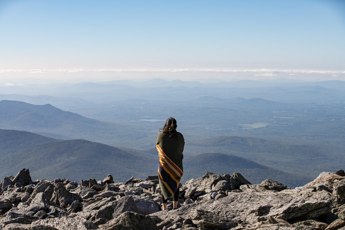A woman looks out over the White Mountains on Mt. Washington in New Hampshire.