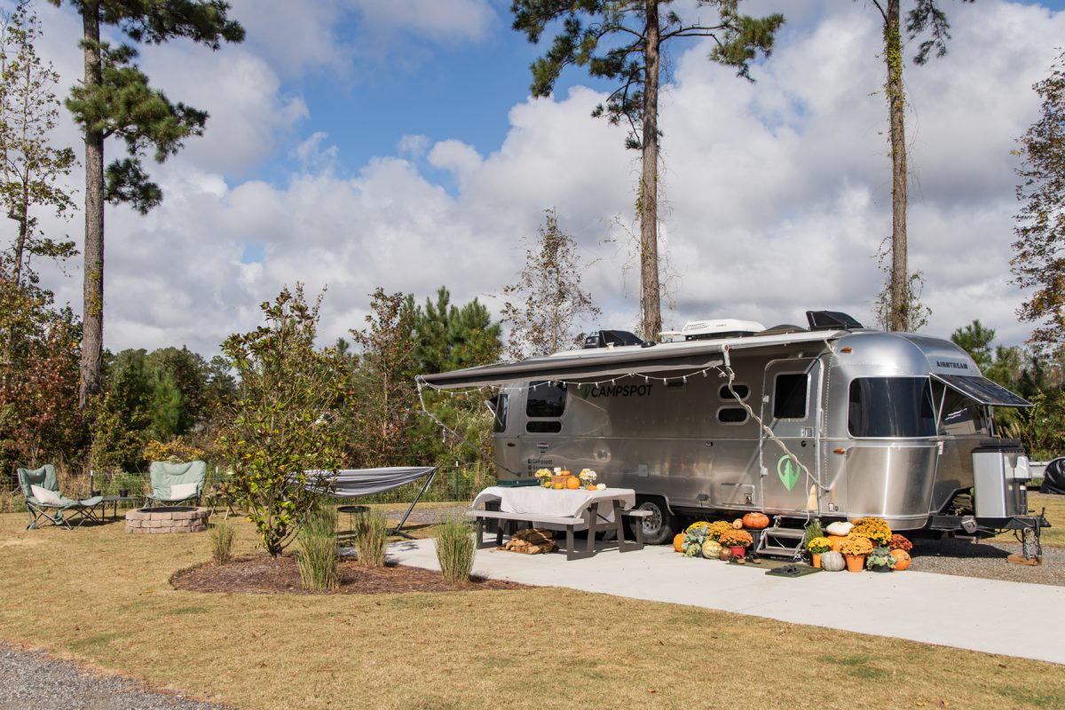 A Campspot Airstream RV sits on an RV site in Carolina Pines RV Resort in Conway, South Carolina. The trailer is decorated with fall pumpkins and decorations.