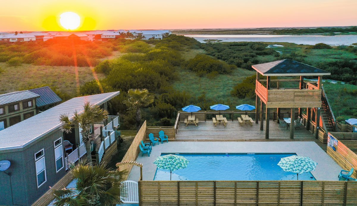 The pool area of the Aloha Beach RV Resort in Port Aransas, Texas, with the sunrise in the distance.