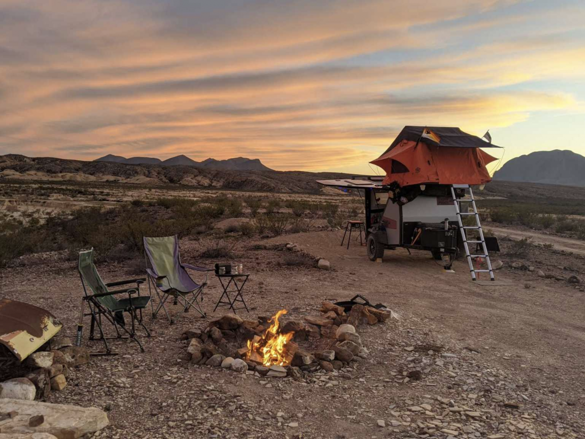 A campsite at Eco-Ranch Rustic Camping Area in Alpine, Texas, with a campfire list and camp chairs set up.