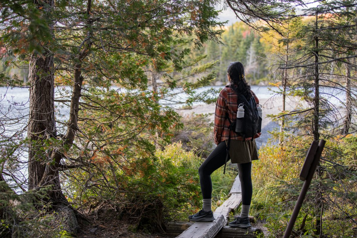 A woman hikes the Sandy Stream Pond Trail in Baxter State Park and overlooks the pond in the distance.