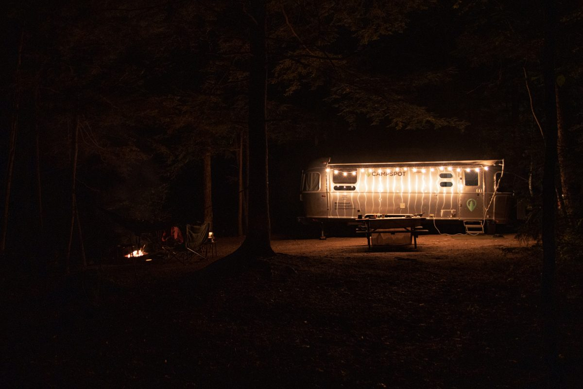 The nighttime depiction of a campsite lit by string lights and a campfire.