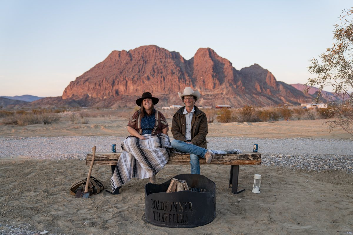 The owners of Roadrunner Travelers Campground in Terlingua, Texas, in front of a campsite and behind Bee Mountain.