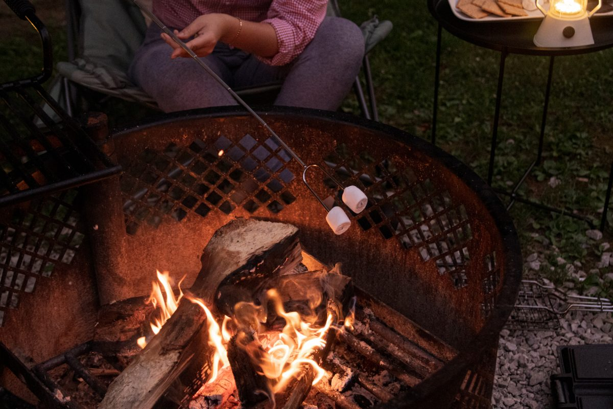 A person roasts their marshmallows on top of a campfire with a lantern glowing in the back.