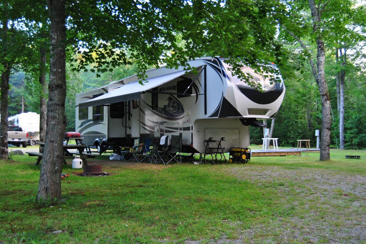A fifth-wheel travel trailer parked in an RV campsite at Forest Ridge Campground in Ellsworth, Maine.