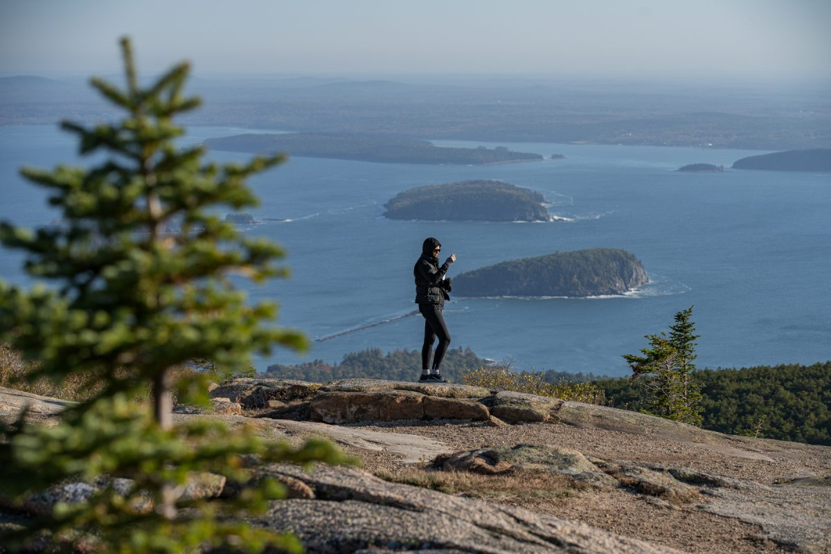 A woman takes a photo from Cadillac Mountain Summit in Acadia National Park in Maine.