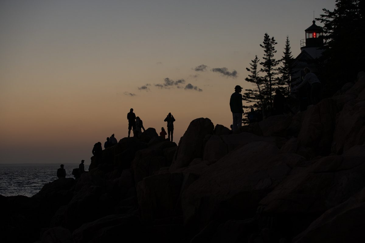 The silhouette of sunset watchers at Bass Harbor Head Lighthouse in Acadia National Park, Maine.