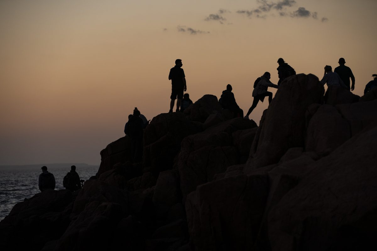 Sunset watchers climb the rocks at Bass Harbor Head Lighthouse in Acadia National Park, Maine.